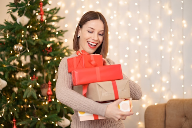 Happy young woman holding many present boxes with christmas tree and lights
