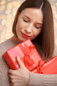 Happy young woman holding many present boxes with lights