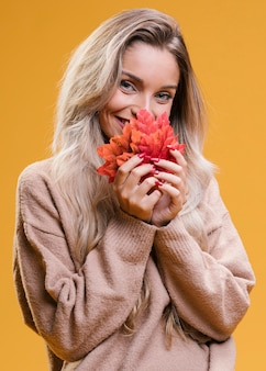 Happy young woman holding maple leaves standing near yellow wall looking at camera
