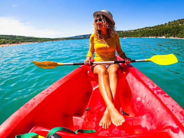 川でカヤックを楽しんでオールを保持している幸せな若い女性。川に漕ぎ、風光明媚な自然を賞賛する帽子とサングラスの白人女性
