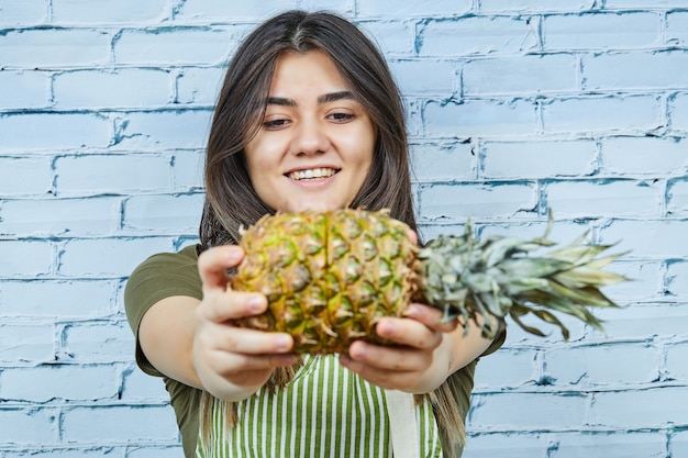 Happy young woman holding pineapple on blue surface