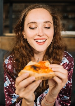 Happy young woman holding pizza slice