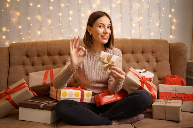 Felice giovane donna in possesso di un presente che mostra segno ok circondato da scatole regalo seduta gambe incrociate