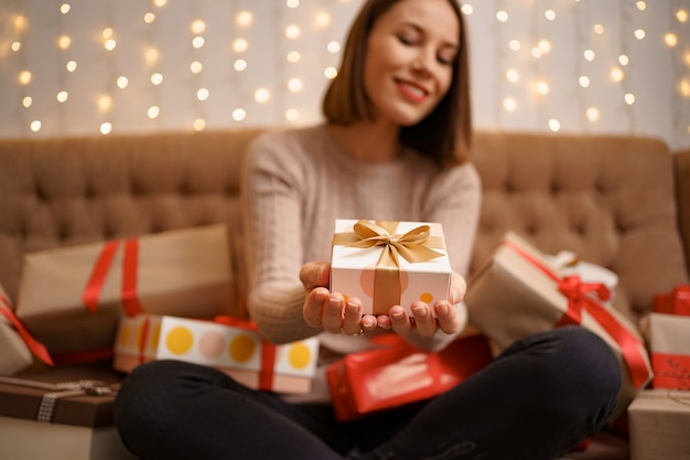 Happy young woman holding a present showing surrounded by gift boxes sitting crossed legs