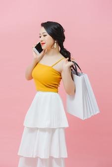 白い背景の上に買い物袋と携帯電話を保持している幸せな若い女性