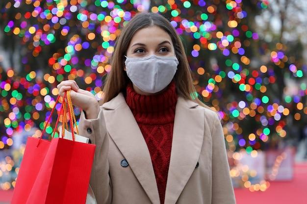 木のクリスマスライトと街の通りを歩いて横に買い物袋を持って幸せな若い女性