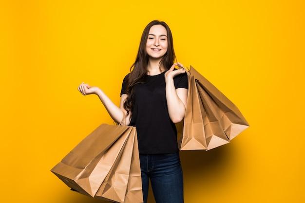 노란색 벽에 쇼핑백을 들고 행복 한 젊은 여자