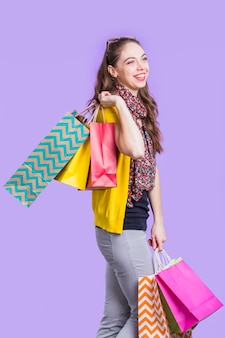 Happy young woman holding shopping bags standing against lavender surface