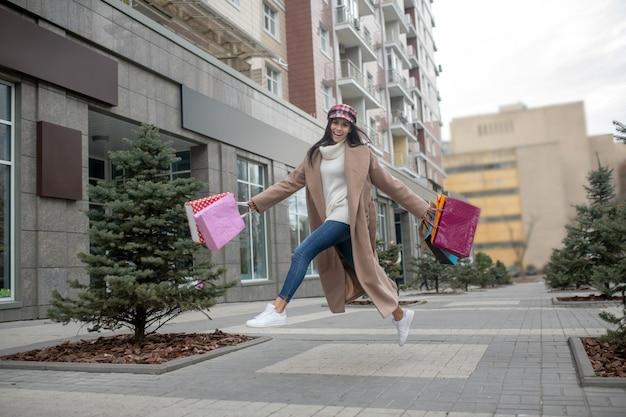 Счастливая молодая женщина, держащая хозяйственные сумки, прыгая на улице