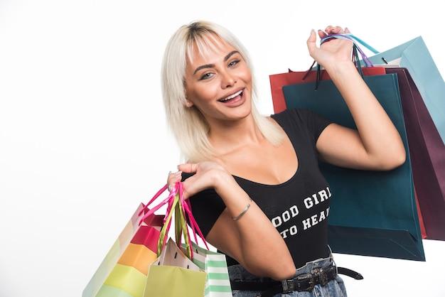 Felice giovane donna tenendo i sacchetti della spesa su sfondo bianco. foto di alta qualità