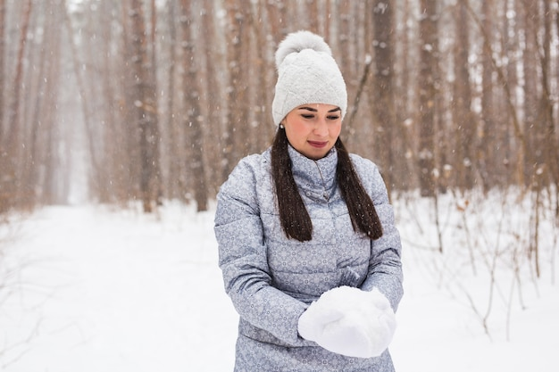 Happy young woman holding snow in winter park