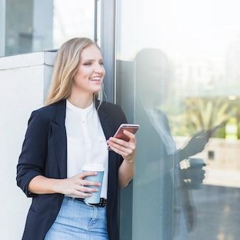 幸せな若い女性は携帯電話を使用してコーヒーカップを取る