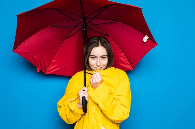 Happy young woman holding umbrella with yellow raincoat and blue wall