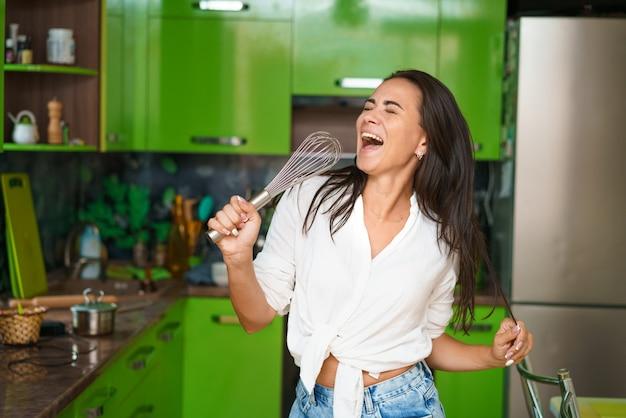 Счастливая молодая женщина, держащая венчик как микрофон, поет песню, танцует, готовит в одиночестве на современной кухне, смешная дама-домохозяйка, веселится, слушая музыку, готовит здоровую утреннюю еду, делает работу по дому