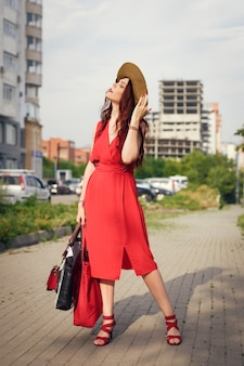 A happy young woman, holding a wide hat, poses in city park in summer