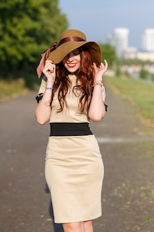 A happy young woman, holding a wide hat, poses in a park in summer