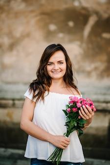 행복 한 젊은 여자는 t- 셔츠를 입고 카메라에 포즈 핑크 장미 꽃다발을 보유하고있다. 옥외. 공원에서 예쁜 여자의 봄 초상화입니다.