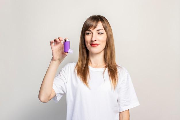 Счастливая молодая женщина держит ингалятор в руке