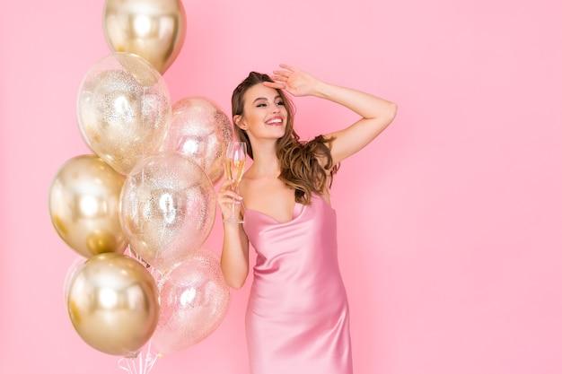 幸せな若い女性は、パーティーのお祝いに来た気球の近くにシャンパンスタンドのガラスを保持します