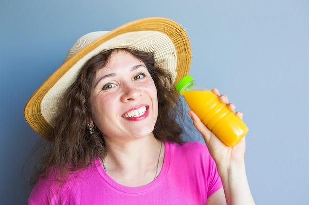 幸せな若い女性はガラス瓶にオレンジジュースを保持します。健康食品、ダイエット、ビタミン、健康的なライフスタイルの概念。