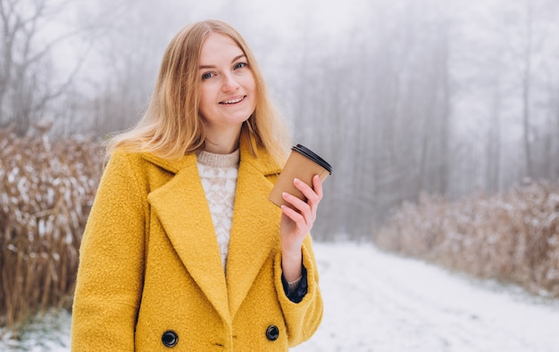 Happy young woman holds paper coffee cup over nature background, trendy color of year 2021 - illuminatiing yellow. take away or delivery concept. copy space.