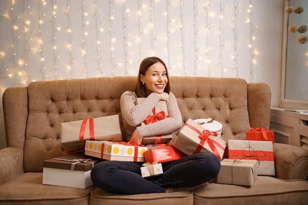 Giovane donna felice che abbraccia molte caselle presenti seduto a gambe incrociate su un divano cammello con luci