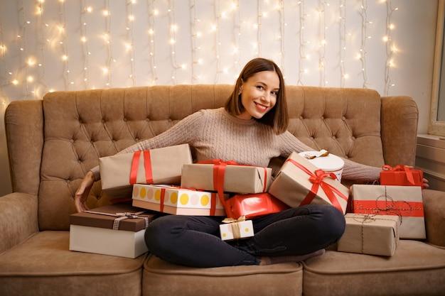 ライト付きのラクダのソファに足を組んで座っている多くのプレゼントボックスを抱き締めて幸せな若い女性
