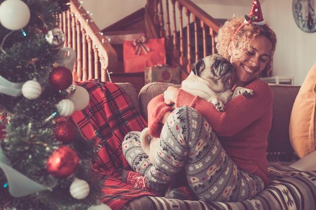 ペットの犬を抱き締めて、クリスマスを祝う幸せな若い女性。自宅でクリスマスを楽しんでいる白人女性とパグ犬。クリスマスを祝うソファで愛犬を抱きしめる陽気な女性