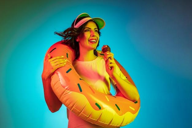 Счастливая молодая женщина в кепке и резиновом кольце с мороженым на модном синем неоне