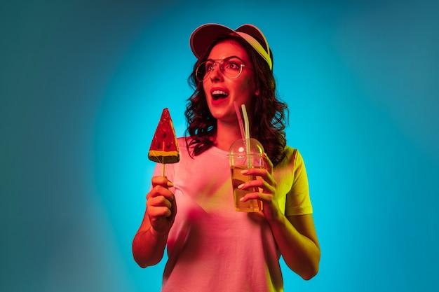 お菓子を保持し、トレンディな青いネオンスタジオで飲む帽子をかぶった幸せな若い女性
