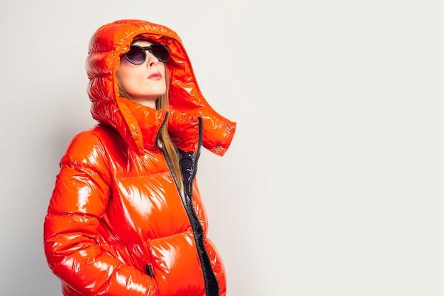 Счастливая молодая женщина в красной куртке и солнечных очках изолированы