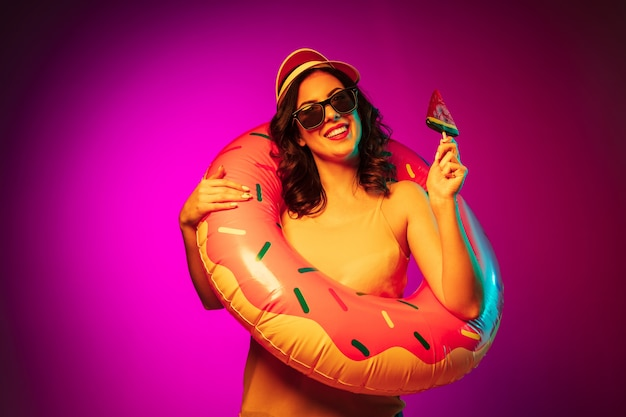 トレンディなピンクのネオンにキャンディーとゴム製のビーチリング、赤いキャップとサングラスで幸せな若い女性