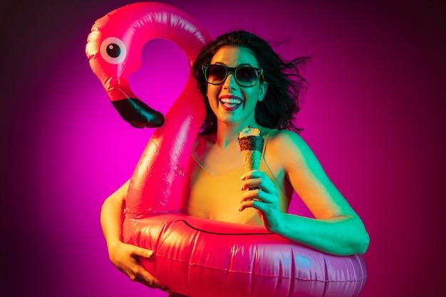Счастливая молодая женщина в резиновом фламинго и солнечных очках с мороженым на модном розовом неоне
