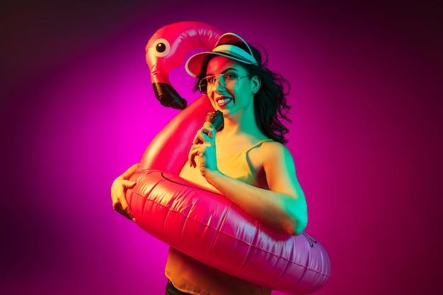 Счастливая молодая женщина в резиновом фламинго, красной кепке и солнечных очках с мороженым на модном розовом неоне
