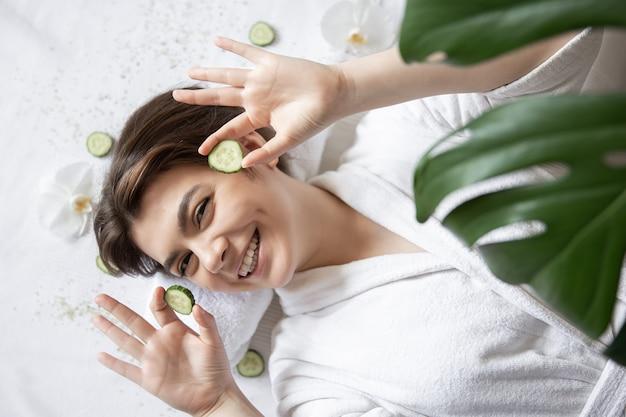 Счастливая молодая женщина в спа-салоне с огурцами на глазах вид сверху