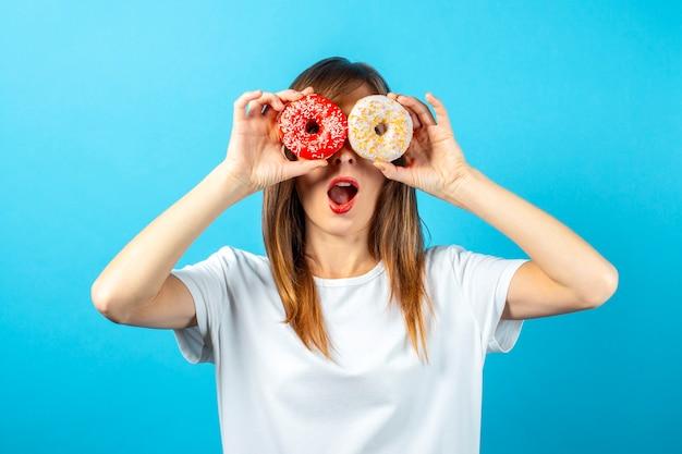 白い空白のtシャツで幸せな若い女性は、孤立した目の前にドーナツを保持します。