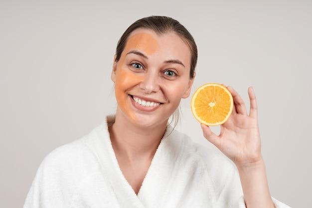 白いローブを着た幸せな若い女性は彼女の顔にオレンジ色のマスクを適用しました