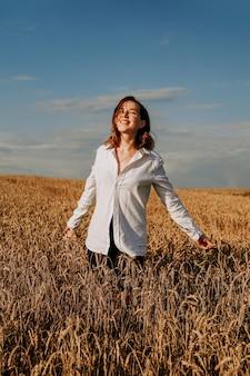 麦畑で白いシャツを着た幸せな若い女性。晴れた日。女の子の笑顔、幸福の概念。横に手を。縦の写真