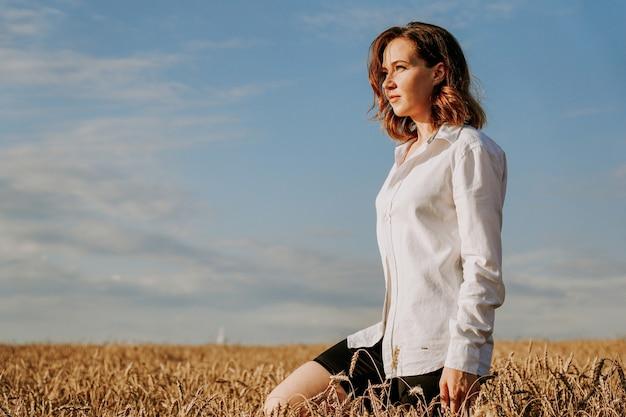 麦畑で白いシャツを着た幸せな若い女性。晴れた日。女の子の笑顔、幸せの概念