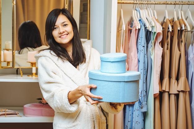 青いボックスを保持し、自宅の楽屋で笑顔のバスローブで幸せな若い女性。ショッピングとファッションのコンセプト。