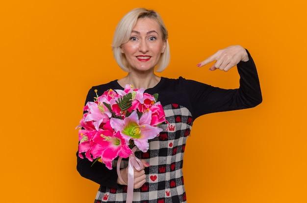 오렌지 벽 위에 서있는 국제 여성의 날을 유쾌하게 축하 미소에 검지 손가락으로 가리키는 꽃의 꽃다발을 들고 아름다운 드레스에 행복 한 젊은 여자