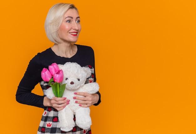 オレンジ色の壁の上に立っている国際女性の日を元気に祝って笑顔を脇に見て贈り物としてチューリップとテディベアの花束を保持している美しいドレスを着た幸せな若い女性