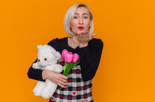 オレンジ色の壁の上に立っている国際女性の日を祝うキスを吹く正面を見て贈り物としてチューリップとテディベアの花束を保持している美しいドレスで幸せな若い女性