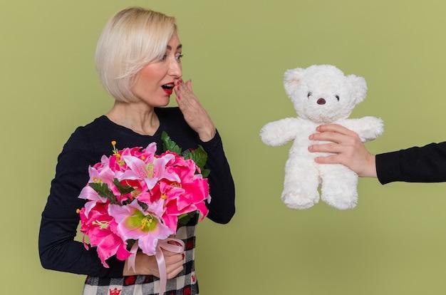 緑の壁の上に立っている国際女性の日を祝う贈り物としてテディベアを受け取りながら、驚きの笑顔に見える花の花束と美しいドレスを着た幸せな若い女性