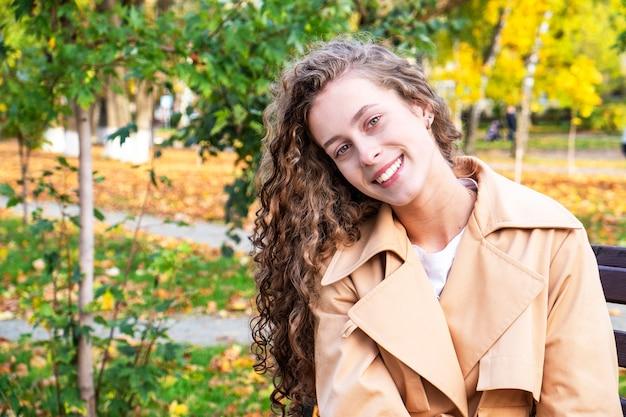 Счастливая молодая женщина в biege пальто. осенний женский портрет. копировать пространство