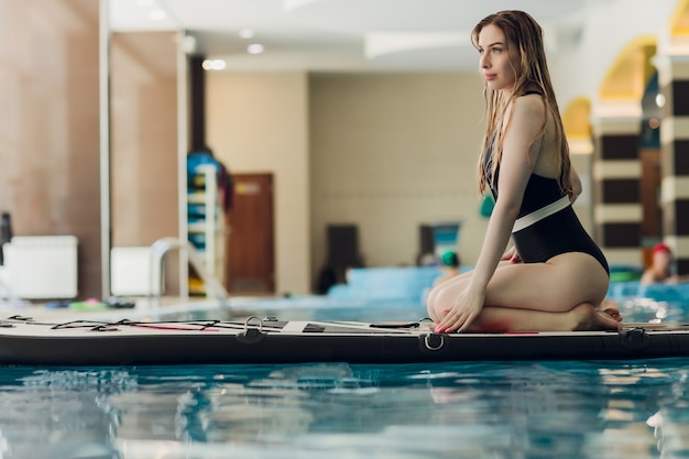 ビキニ姿の幸せな若い女性が屋内サーフィン施設のプールインストラクターのサーフボードで日光浴をしています...