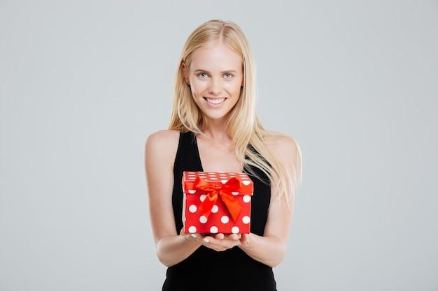 Счастливая молодая женщина в черном платье, держащая подарочную коробку, изолированную на белом фоне