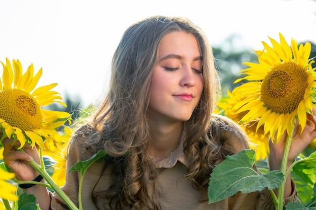 개화 해바라기에 행복 한 젊은 여자