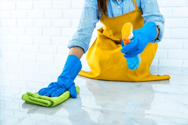 Счастливая молодая женщина в голубой резине используя ткань пока очищающ на поле дома