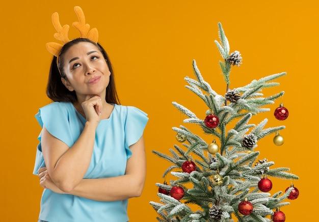 オレンジ色の背景の上のクリスマスツリーの横に前向きに立っていると考えて見上げる鹿の角で面白いリムを身に着けている青いトップの幸せな若い女性